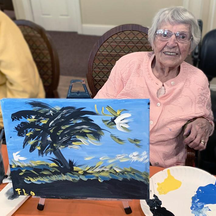 Senior showing painting at Madison at Oviedo