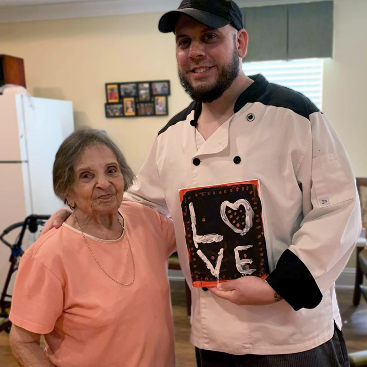 Chef Dominick and resident holding love sign at Madison at Oviedo