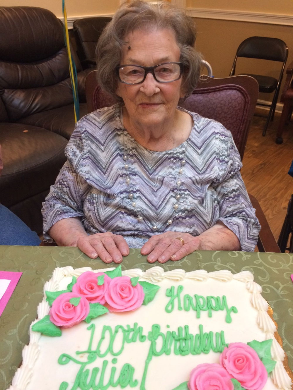 Angels for the Elderly memory care resident with blueberry dream cake celebrating 100th birthday