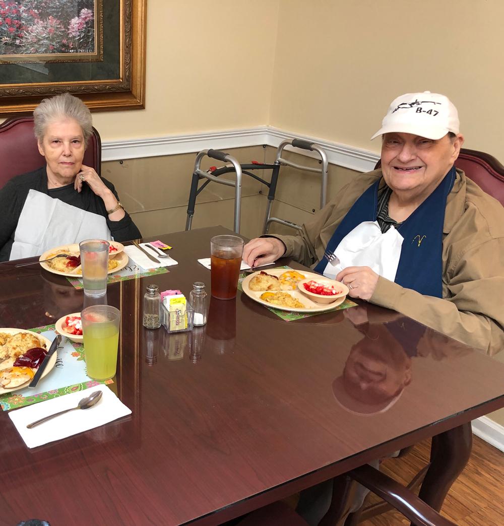 Senior living residents eating caramel icing at Angels for the Elderly