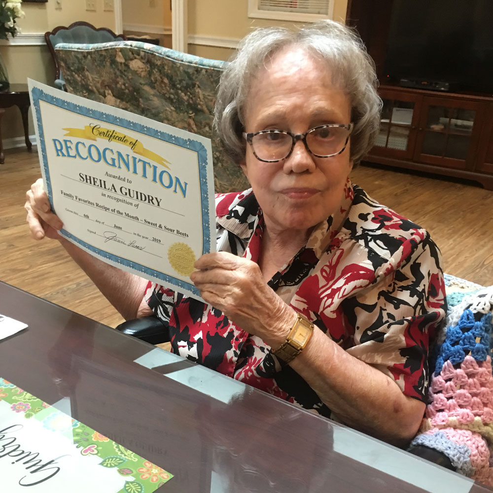 Memory care resident with certificate of recognition at Angels for the Elderly in Montgomery, AL
