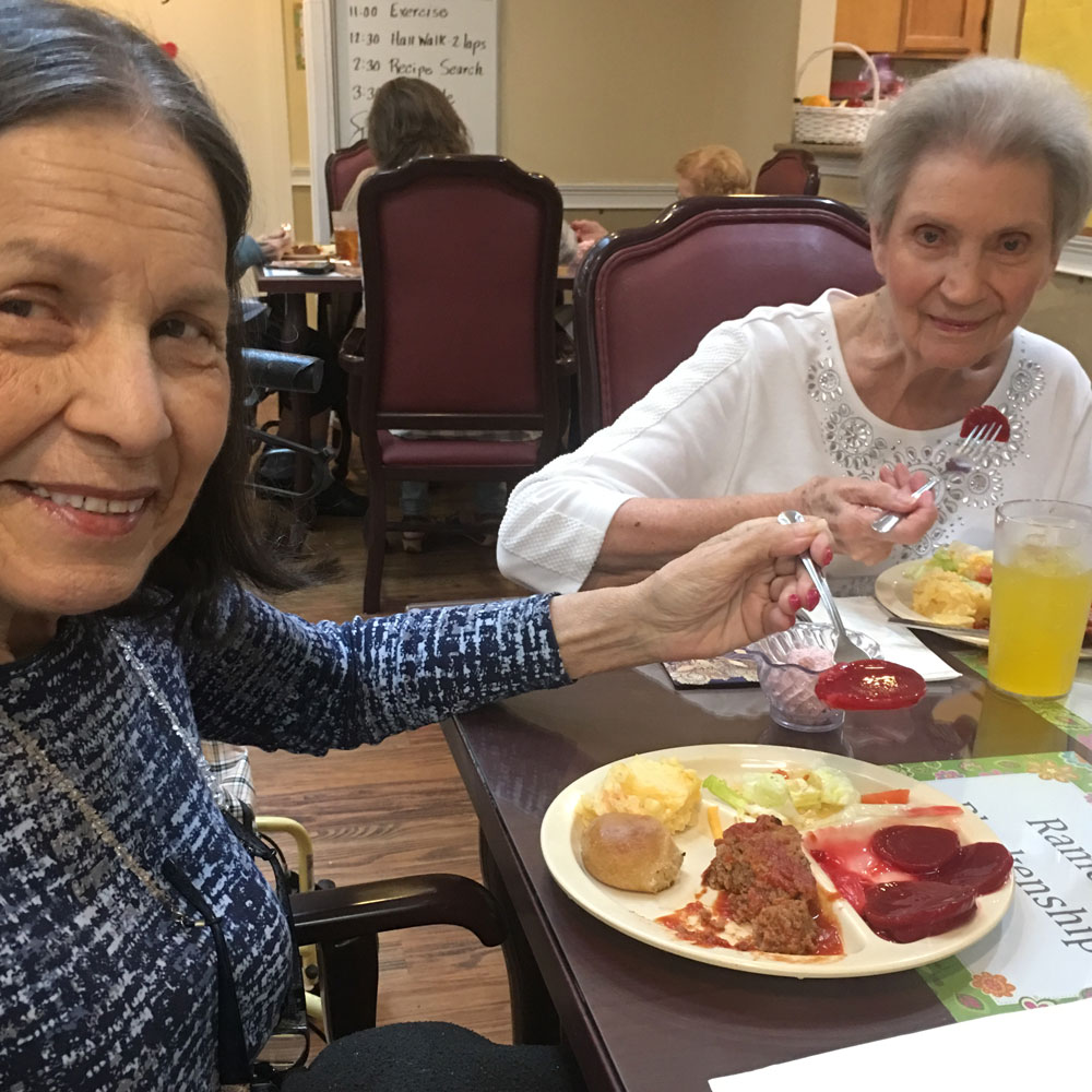 Memory care residents enjoying meatloaf at Angels for the Elderly in Montgomery, AL