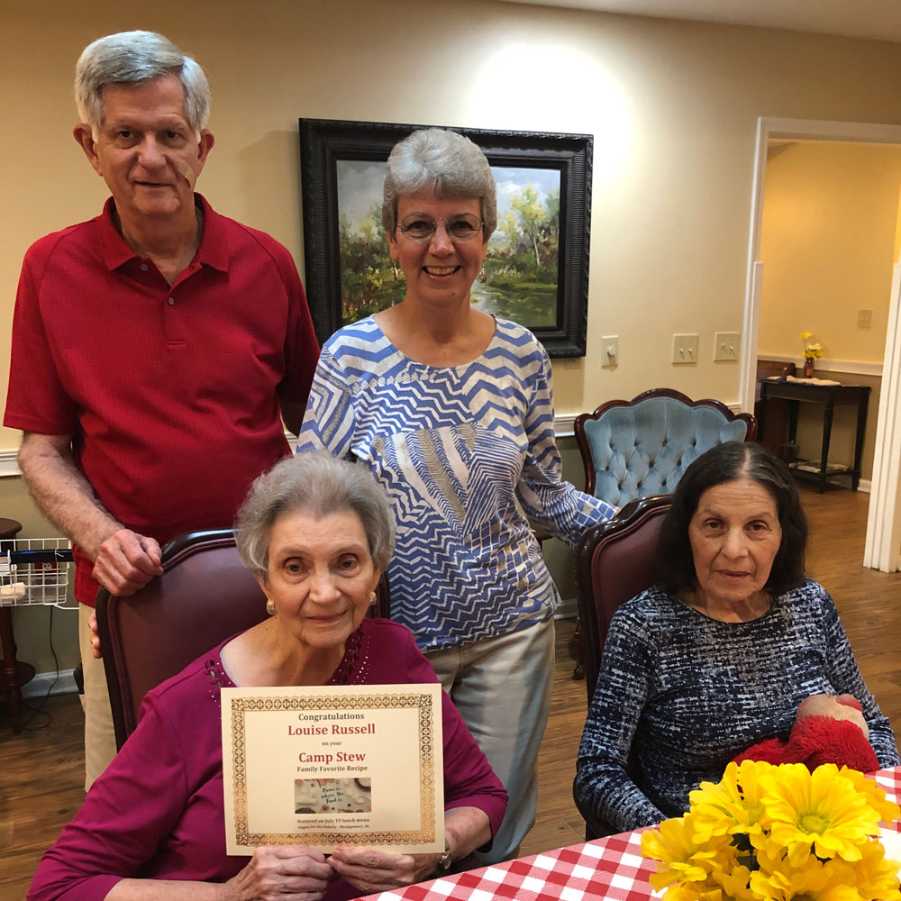 Memory care resident holding recipe certificate with family at Angels for the Elderly