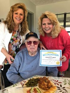 Angels for the Elderly memory care resident with family members holding certificate in Montgomery, AL