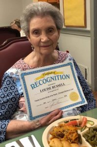 Angels for the Elderly memory care resident holding certificate in Montgomery, AL