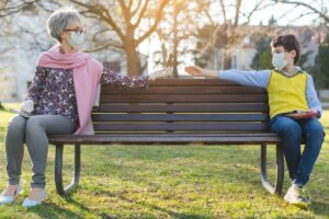 Lake Howard Heights | Senior social distancing with grandson on bench