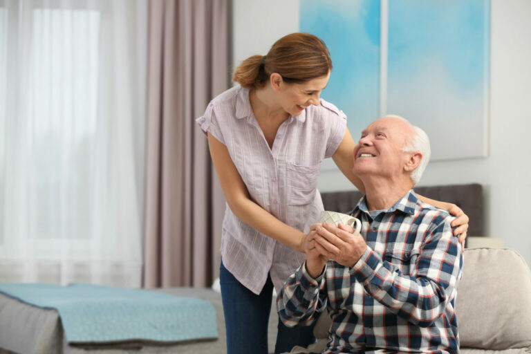 Legacy Ridge at Alpharetta | Elderly man with cup of tea near female caregiver at home.