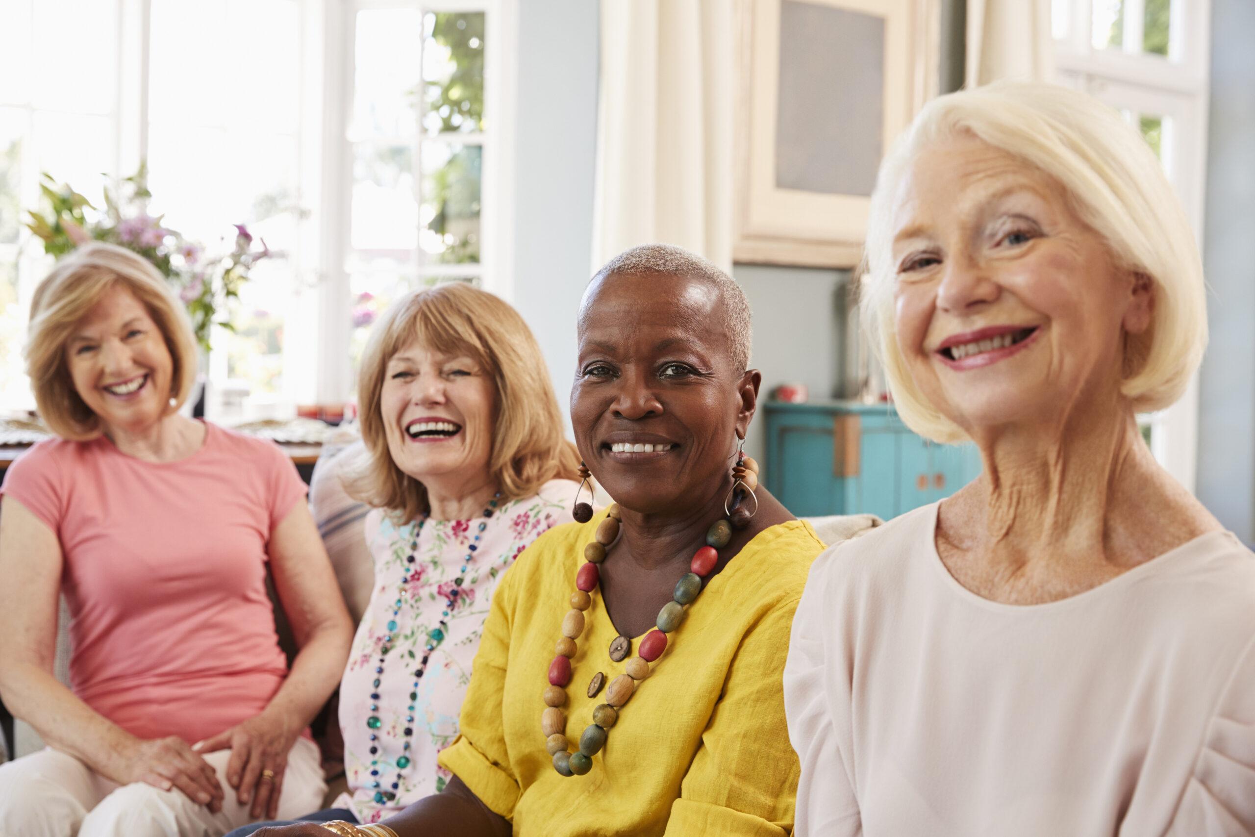 Legacy Ridge at Buckhead | Portrait Of Senior Female Friends Relaxing On Sofa At Home