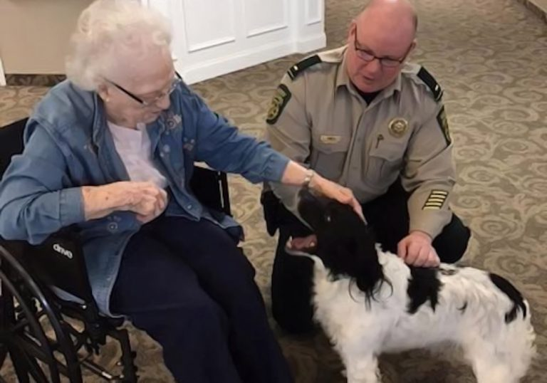 Legacy Ridge at Sweetwater Creek resident petting therapy dog with sheriff
