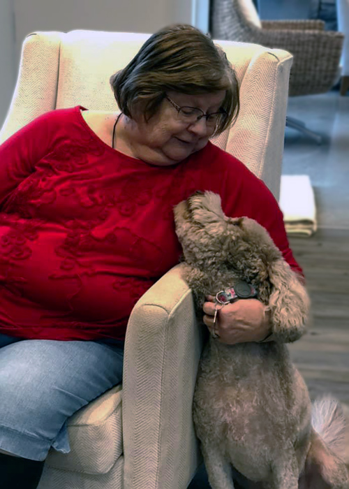 Legacy at Savannah Quarters senior resident petting dog