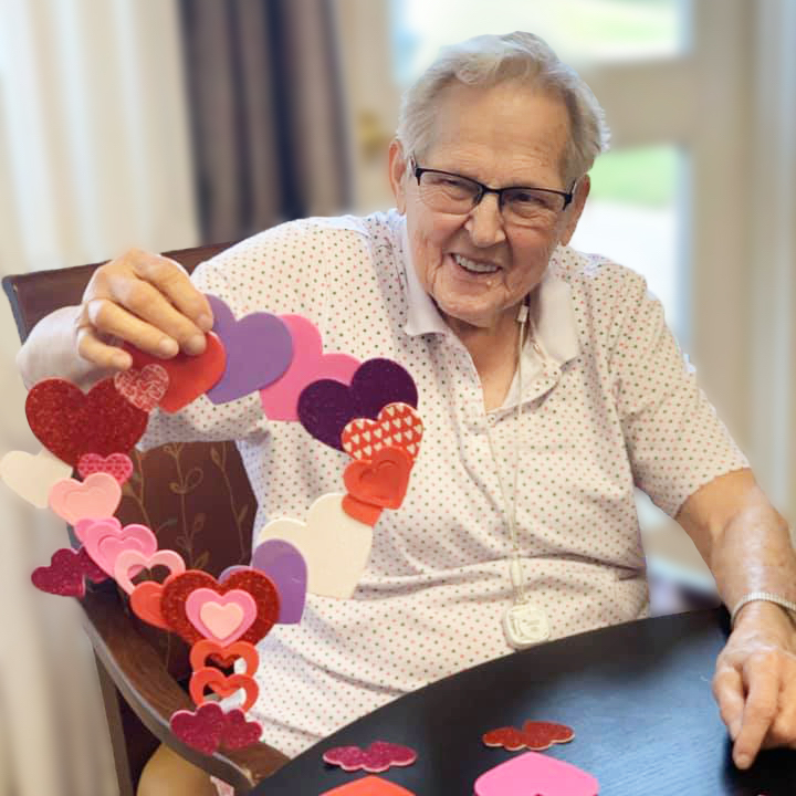 Madison at Clermont resident holding Valentine's Day craft