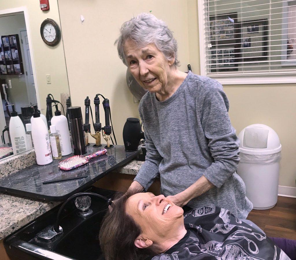 Memory care resident washing associate's hair at Madison Heights at The Prado in Macon, GA
