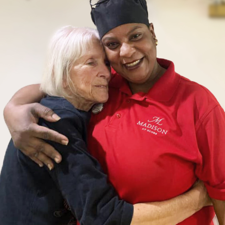 Madison at Ocoee senior resident embracing dining services director in Ocoee, FL