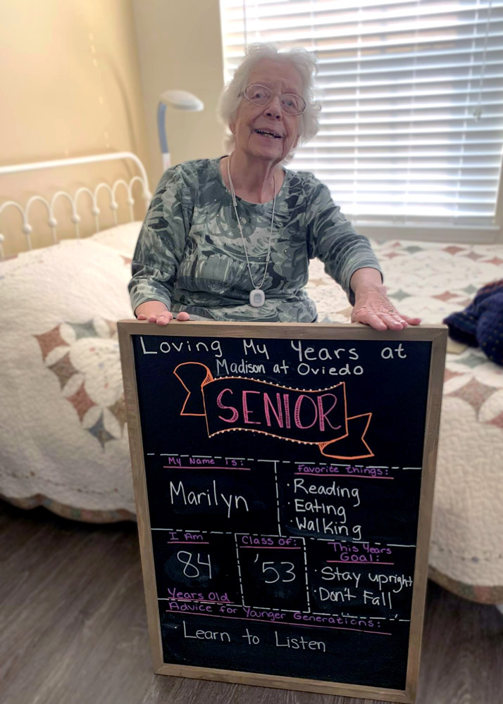 senior living resident holding board at Madison at Oviedo