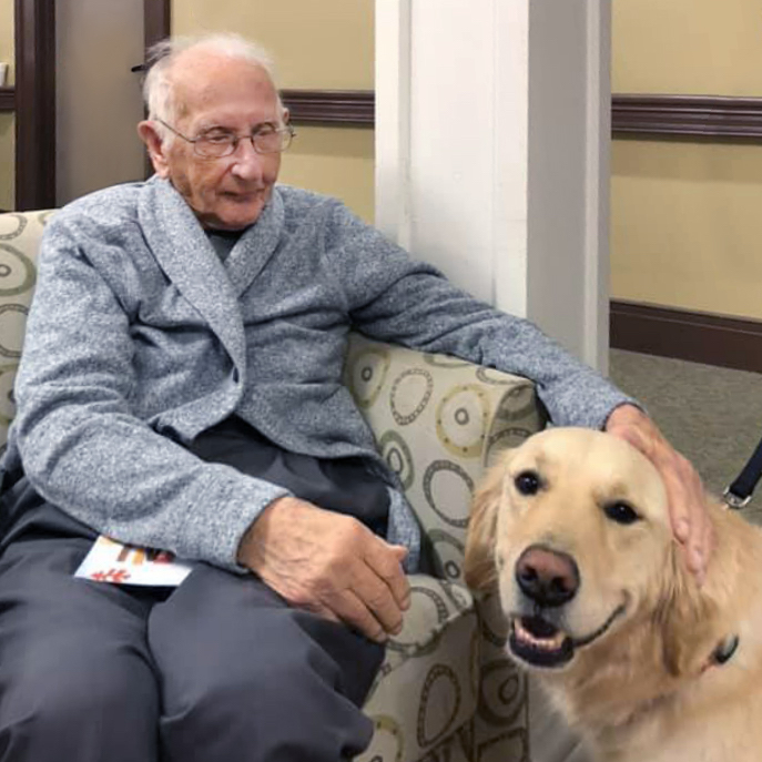 Spring Park senior living resident petting therapy dog in Travelers Rest, SC