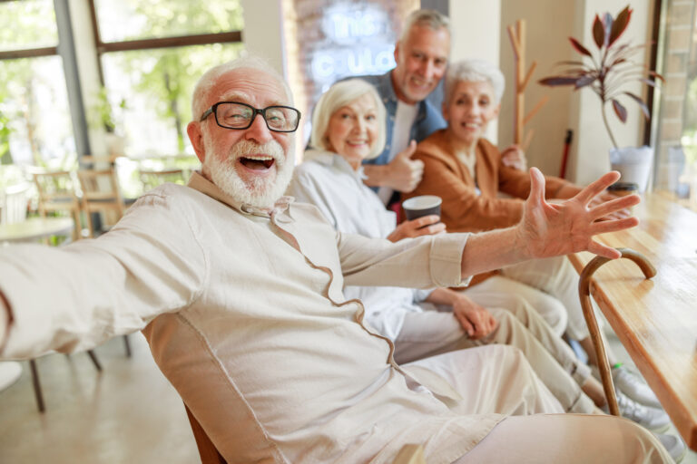 The Goldton | Cheerful seniors making selfie in cafe