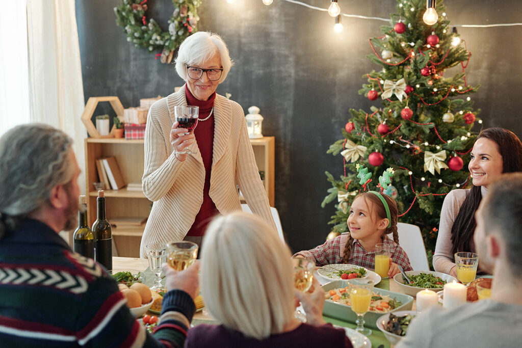The Goldton at St. Petersburg | Happy senior woman with glass of wine making Christmas toast by family dinner