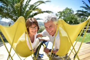 The Goldton at St. Petersburg   Senior couple lounging in lawn chairs surrounded by palm trees, outdoors