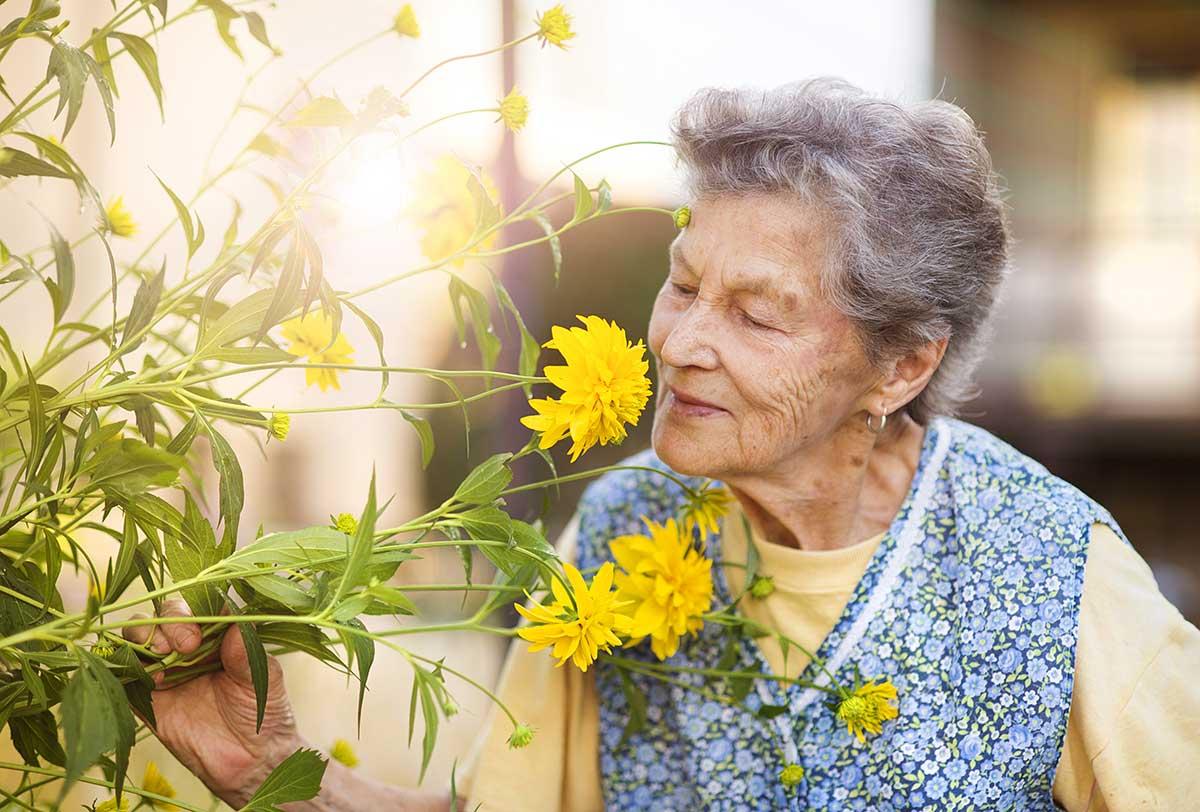 Atlas Senior Living | Woman smelling flowers