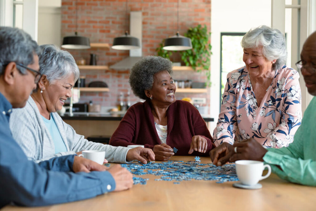 Atlas Senior Living | Group of seniors socializing, while doing a puzzle